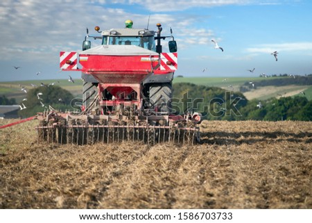 Rear View Of Tractor Pulling Drill Sowing Wheat Seed