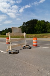 Rear view of traffic barricade and safety barrels, asphalt roadway copy space, blue sky and trees, vertical aspect