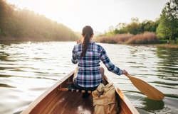 Rear view of travel girl paddling wooden canoe on the sunset lake