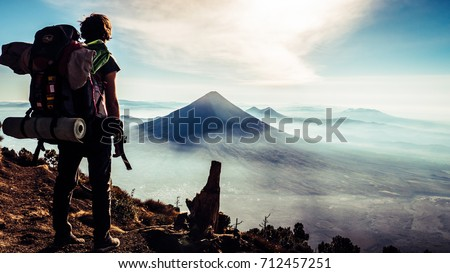 Rear view of traveler guy with backpack looking amazing view of Guatemala mountains. Pick of Volcàn de Agua with one person enjoying the beautiful panorama. Wanderlust vacation concept with adventure