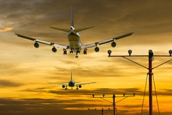rear view of two airplanes for commercial passenger or cargo transportation aircraft flying in sequence and spread the wheel for landings to airport on golden sunset sky in dusk or evening