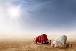 Rear view of two asian muslim man praying in prostration position on desert with sun rays and dark sky background