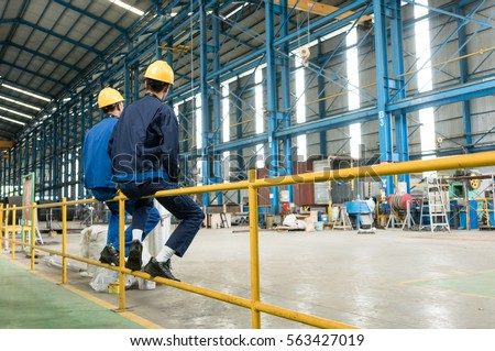 Rear view of two blue-collar workers during break in the interior of an industrial hall