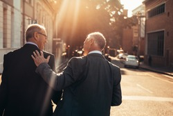 Rear view of two business people walking outdoors and talking next to an office building after a successful business meeting. Senior business professionals walking together on a sunny day.