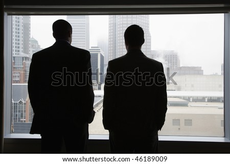 Rear view of two businessmen as they stare out a large window with a city view. They have their hands in their pockets. Horizontal view.