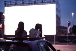 Rear view of two female friends sitting in the car while watching a movie in an open air cinema with a big white screen. Entertainment concept. Focus on people. Horizontal shot