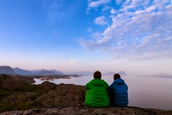 Rear view of two friends sitting together on clief near ocean, midnight sun time, Lofoten island, Norway