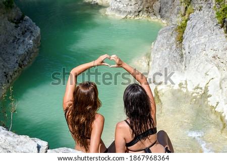 Rear view of two girld sitting on rock  above lake, making heart shape with hands. Kotli, Istria, Croatia. Zdjęcia stock ©