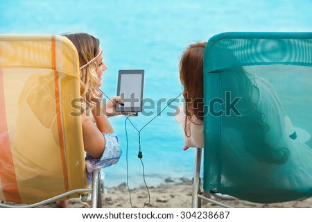 Rear view of two girls listening to music on digital tablet while sunbathing on the beach
