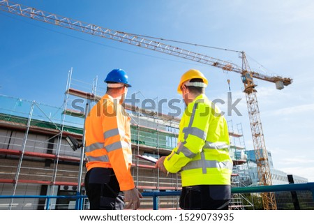 Rear View Of Two Male Architect Wearing Hardhat Looking At Construction Site