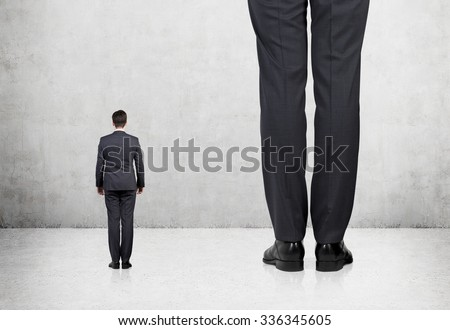 Rear view of two professionals in formal suites who stand in front of concrete wall. #336345605