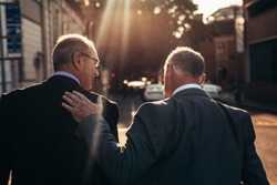 Rear view of two senior businessman walking together outdoors on city street. Mature businessman with hand in back of male colleague walking outdoors on a sunny day.