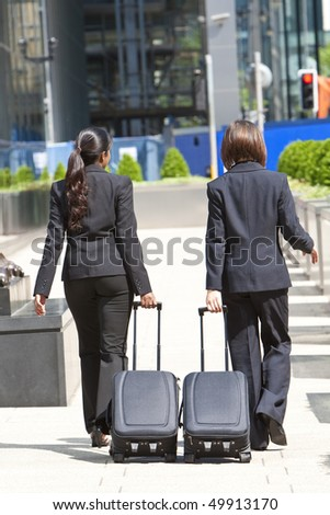 Rear view of two young women business executives wearing suits walking through a city with rolling suitcases.
