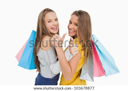 Rear view of two young women the thumb-up with shopping bags against white background