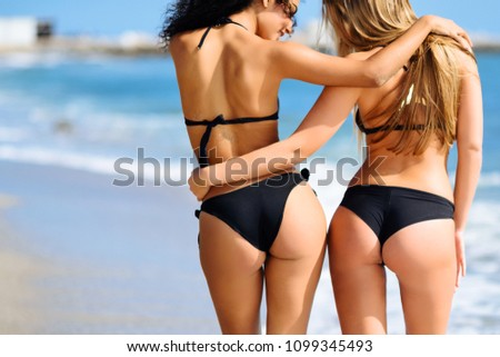 Rear view of two young women with beautiful bodies in bikini having fun on a tropical beach.
