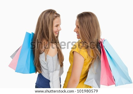 Rear view of two young women with shopping bags against white background