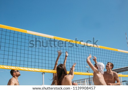 Rear view of unrecognizable caucasian males and females playing amateur beach valleyball, ball flying in the air against blue sky background.