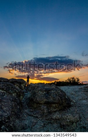 Rear view of unrecognizable male photographer taking pictures of the sunset over the Stone Mushrooms near Beli Plast village, Kardzhali Municipality, Bulgaria
