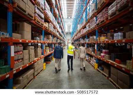 Rear view of warehouse team discussing while walking in warehouse #508517572