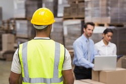 Rear view of warehouse worker in front of his managers in a large warehouse