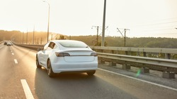 Rear view of white electric car moving along aspalted city road in sunlights, widescreen. Luxury and success concept