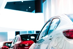 Rear view of white luxury car parked in modern showroom for sale. White shiny car on blurred red car in showroom. Car dealership. Coronavirus impact on automotive industry concept. Showroom interior.