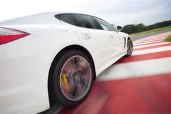 Rear view of white Sportcar  fast drive on racetrack.