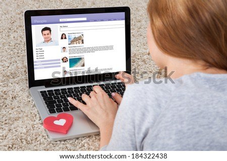 Rear View Of Woman Chatting On Social Networking Sites Using Laptop