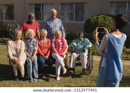 Rear view of woman clicking photo of diverse group of senior people with mobile phone in the park