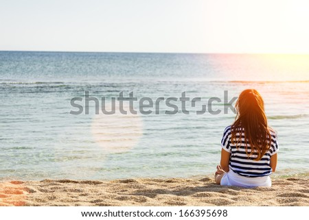 Rear view of woman enjoys a sunny day relaxing on the beach.Copy space,lens flare