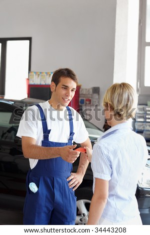 Rear view of woman giving credit card to mechanic. Copy space