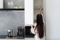 Rear view of woman in homewear taking glass cup from shelf in white cupboard with dishware in minimalist kitchen with built in appliance, preparing morning coffee at home