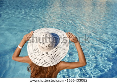 Rear view of woman in white hat sitting near pool on a sunny day. Sea travel concept with place for your text. stock photo