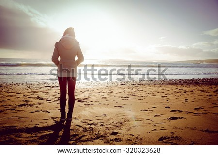 Rear view of woman looking at the sea during the sunset on the beach in front of camera #320323628