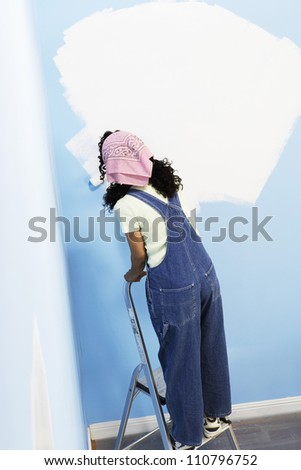 Rear view of woman on stepladder painting her new house