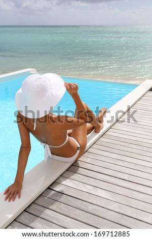 Rear view of woman sitting by pool in white bikini - Shutterstock ID 169712885