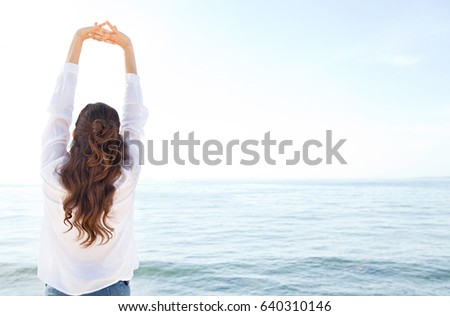 Rear view of woman stretching her arms up, breathing fresh air contemplating blue sea, relaxing in coastal exterior. Healthy wellness nature lifestyle, serene morning by the ocean, space background.