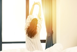 Rear view of woman stretching in bed after wake up in morning with sunlight