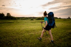 rear view of woman with backpack and sticks who walking along grassy field towards the forest. Skyline in background.