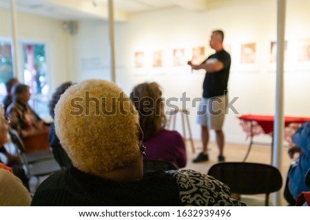 Rear view of woman with blonde dreadlocks hair sitting with audience and listening to speech by male speaker at world and spoken word festival Stock photo ©