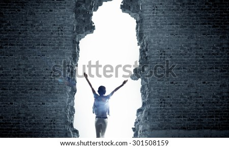 Shutterstock Rear view of woman with hands up entering crack in wall