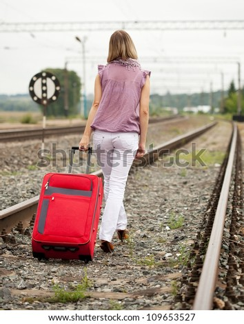 Rear view of woman with luggage walking on rail road