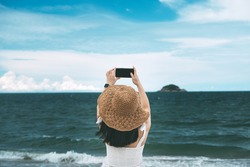 Rear view of young adult asian woman relax in nature on beach sand with blue sky and sea. Using mobile phone for internet social media. Outdoor travel at southeast asia, Thailand.