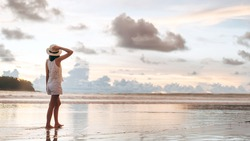 Rear view of young adult tourist asian woman walking relax on beach sand with beautiful dramatic sunset sky. Outdoor domestic travel at tropical ocean
