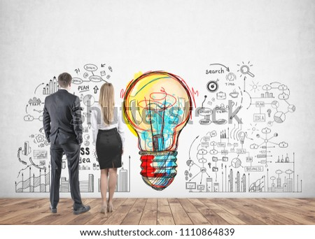 Rear view of young and successful business partners wearing suits looking at a bright colorful light bulb with business scheme icons drawn on a concrete wall - Shutterstock ID 1110864839