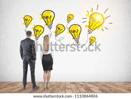 Rear view of young and successful business partners wearing suits looking at a concrete wall with many lightbulbs. One is lit. A bright idea concept #1110864806