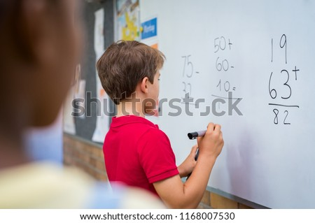 Rear view of young boy solving addition and subtraction on white board at school. Schoolboy thinking while solving math's sum. Child writing the solution of the mathematical operation in classroom.