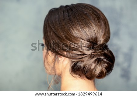 Rear view of young brunette woman with beautiful middle bun hairstyle on gray background Foto stock ©