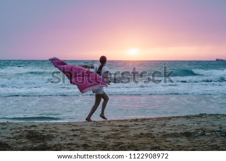 Rear view of young brunette woman with pink towel running on the beach near the stormy sea with waves on beautiful pink and purple sunset. Wallpaper. Sunset on the sea, ocean. #1122908972