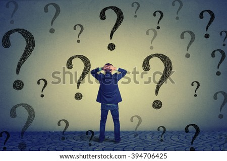 Rear view of young business man with hands on head standing in front of wall with many questions wondering what to do next. Full length of businessman facing the wall. Job work challenge concept